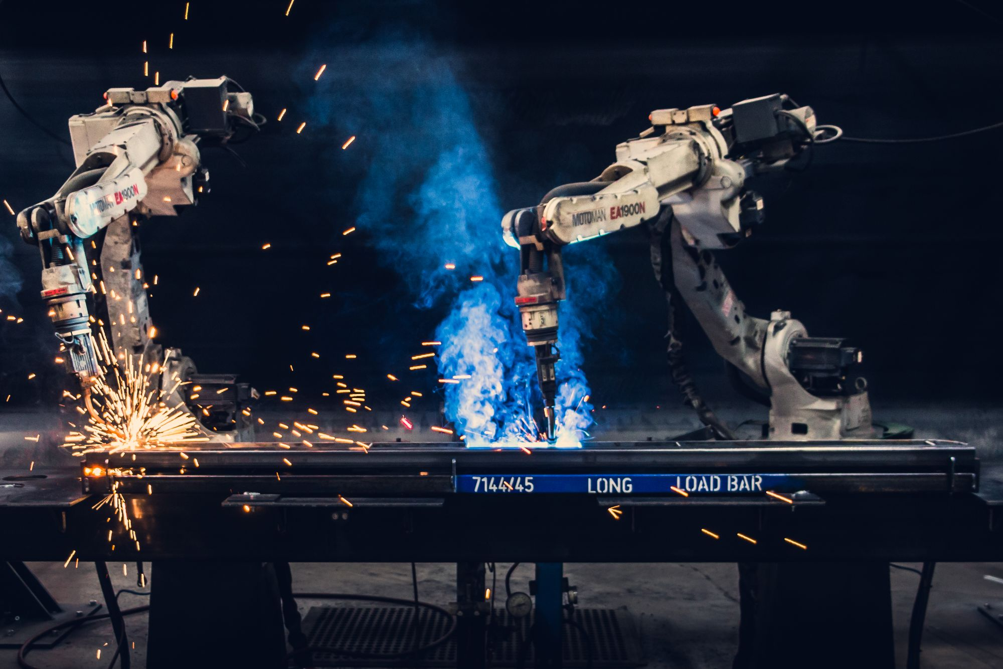 Two automated robot arms welding a long steel bar